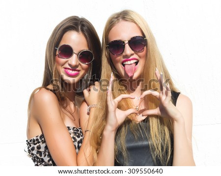 Two young girl friends standing together and having fun,showing signs with their hands. Going crazy,positive emotions.Looking at camera.Two pretty young women in trendy sunglasses and cocktail dresses - stock photo