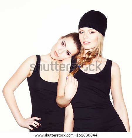 Two young girl friends standing together. Brunette put her head on the blonde's shoulder, looking at camera. Inside - stock photo