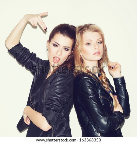 Two young girl friends standing together. Brunette showing sign with her hand. Both looking at camera. Inside - stock photo