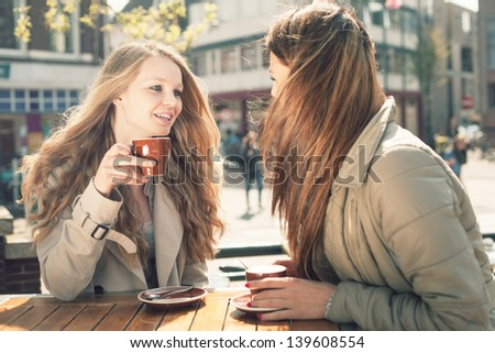 Two young girl-friends talking and drinking coffee in cafe, outdoors - stock photo