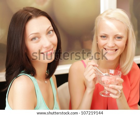 Two young girl having coffee break and eating ice cream - stock photo