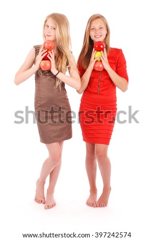 Two young girl holds an three apples isolated on white - stock photo