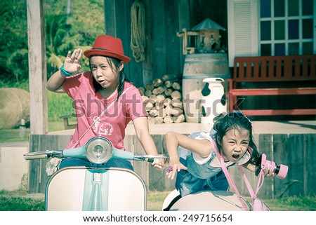 two young girl ride motor/cross process style - stock photo