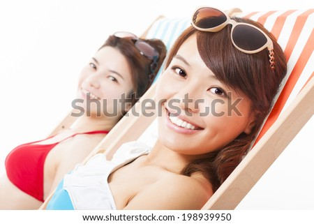two young girl sunbathing and lying on a beach chair - stock photo