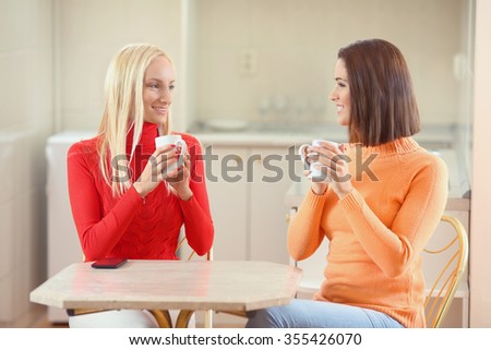 Two young girlfriends having a cup of coffee at home
