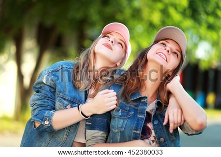 Two young girlfriends in sunglasses look up. Lifestyle. Summer outdoor
