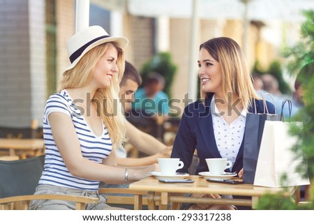 Two young girlfriends sitting in a cafe chatting and relaxing after successful shopping - stock photo