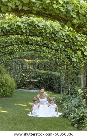 Two young girls and mid adult bride squatting under ivy arches, portrait