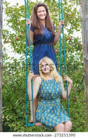 Two young girls are riding on handmade swing in summer apple trees garden - stock photo