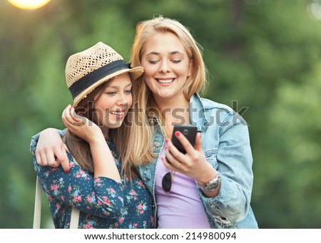 Two young girls are using phone outdoors - stock photo