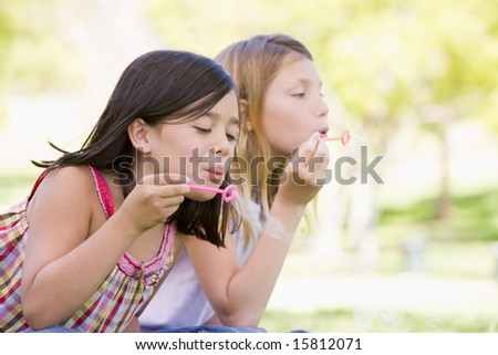 Two young girls blowing bubbles outdoors - stock photo