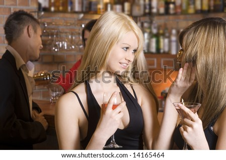two young girls chatting and drinking in a pub