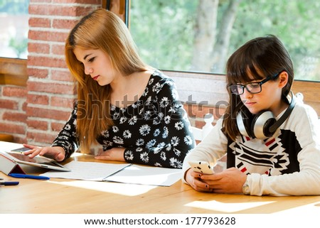 Two young girls concentrating on digital devices at desk. - stock photo