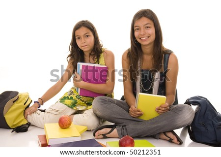 Two young girls doing school homework isolated on white - stock photo
