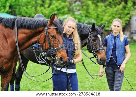 Two young girls - dressage riders with horses - stock photo