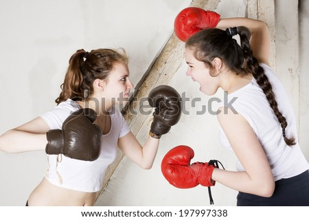 two young girls dressed as boxers are fighting - stock photo