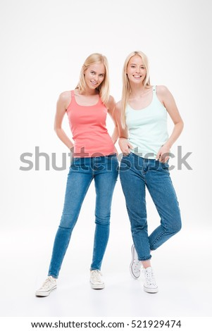 Two young girls dressed in t-shirts and jeans posing. Isolated over white background. Looking at the camera.