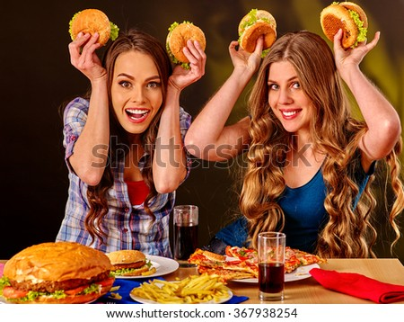 Two young girls eating fastfood in cafe.