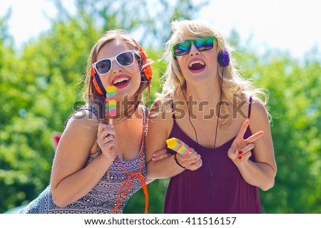 Two young girls eating ice cream and having fun on the street