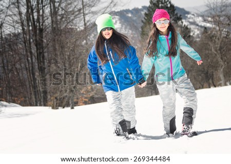 Two young girls enjoy walking in the snow - stock photo