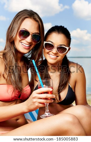 Two young girls enjoying rest on the beach