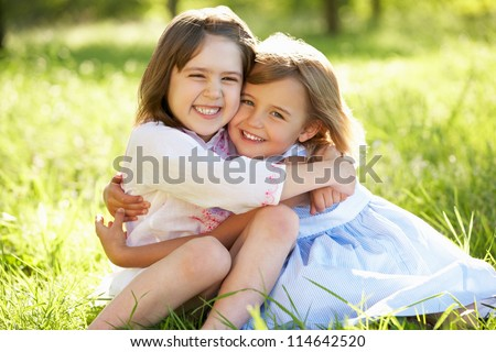 Two Young Girls Giving One Another Hug In Summer Field - stock photo