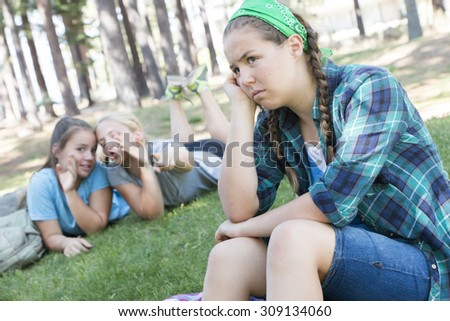 Two Young Girls Gossiping about another Girl - stock photo
