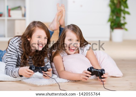 Two young girls happily playing video games in a console laying on the living-room floor - stock photo