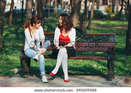 Two young girls having fun while sitting on a bench in a park - stock photo