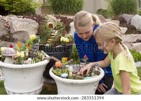 Two young girls helping to make fairy garden in a flower pot - stock photo