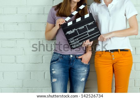 Two young girls holding a clapboard against brick wall with copy-space - stock photo