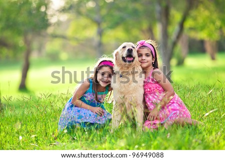 Two young girls hugging golden retriever dog in the park - stock photo