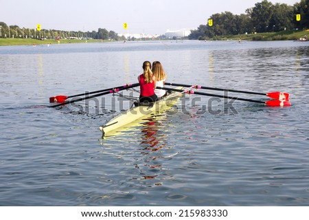Two young girls in a boat, paddles on the tranquil lake - stock photo