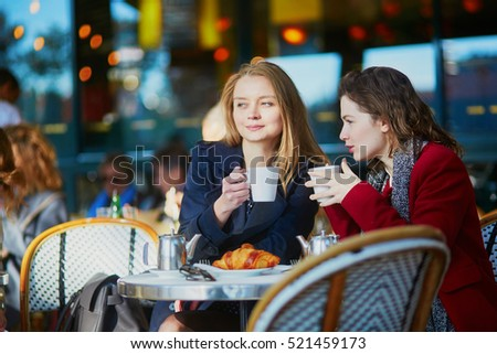 Two young girls in Parisian outdoor cafe, drinking coffee with croissant and chatting. Friendship concept