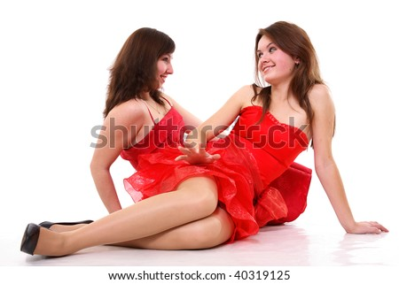 Two young girls in red dresses sitting opposite each other