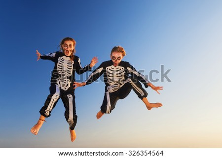 Two young girls in scary skeleton costumes jumping with fun high in air before Halloween night party on sunset sea beach. Active people, lifestyles and event celebrations on tropical holidays. - stock photo