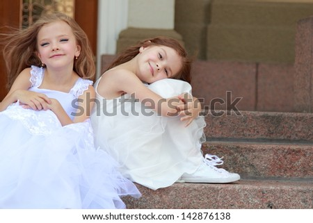 Two young girls in white wedding dresses sitting on the steps outside the building outdoors - stock photo