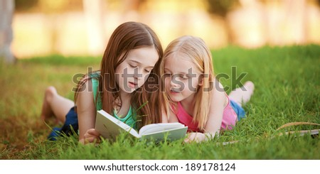 Two young girls lying on the grass outdoors reading a book.  These siblings are enjoying time together as family during summer - stock photo