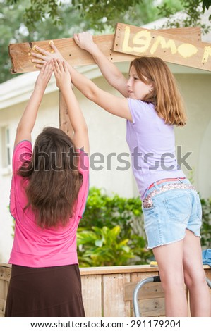 Two young girls painting a lemonade stand sign - stock photo