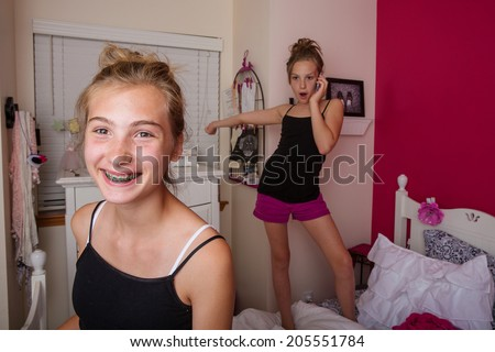 Two young girls playing and talking on the phone in their pink bedroom. - stock photo