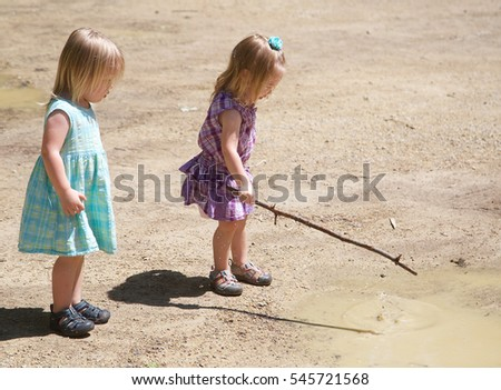 Two young girls playing in mud with dresses