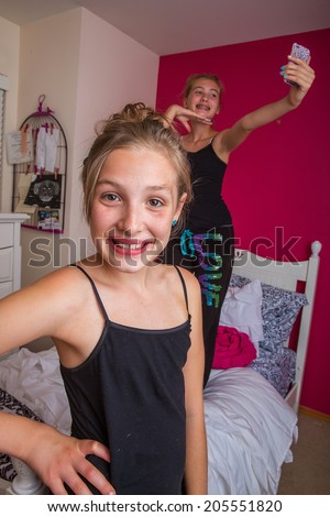 Two young girls playing in their room taking a selfie - stock photo