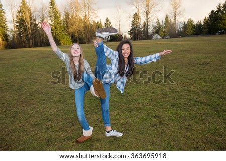 Two young girls playing outside - stock photo