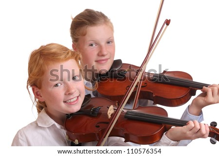 Two young girls playing violin on white background - stock photo