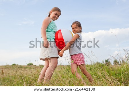 Two young girls playing with a ball outdoors