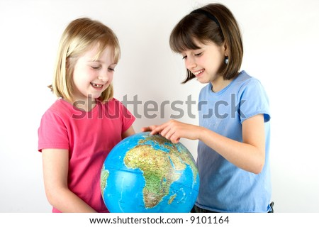 Two young girls pointing at a globe against white background
