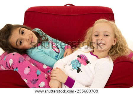 Two young girls relaxing in winter pajamas - stock photo