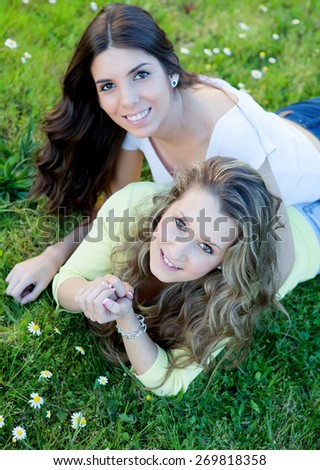 Two young girls resting on the grass. The best friends - stock photo