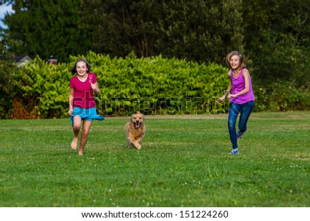 Two young girls running fast with a golden retriever dog - stock photo