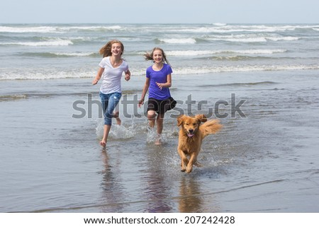 two young girls running on the beach with their golden retriever dog